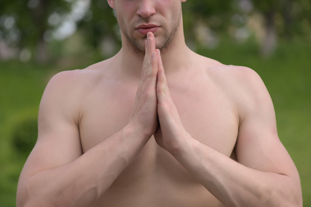 Man with muscles holds his hands together on green trees background, selective focus. Concept of yoga and health