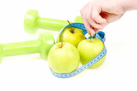 Trio of apples wrapped with cyan flexible ruler in female hand and green dumbbells lying nearby isolated on white background. Concept of sports, diet and slim shape Stock Photo