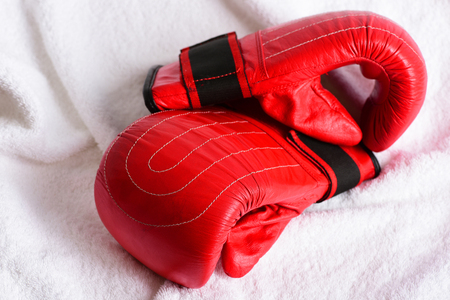 Red boxing gloves on white towel background, close up. Concept of sportive lifestyle and strength Stock Photo