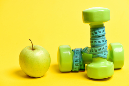 Food and sport. Apple in green colour with lightweight dumbbells and cyan measuring tape wrapped around it, isolated on yellow background. Dieting and vegetarianism concept