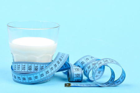 Milk in glass and tape for measuring, isolated on light blue background with copy space