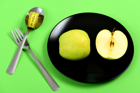 Apple halves set lying on black ceramic plate near shiny metal cutlery with roll of yellow tape for measurement isolated on light green background. Concept of healthy food and dieting