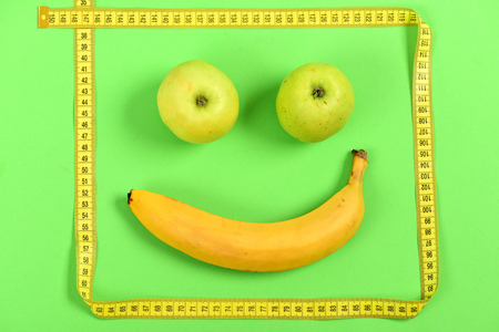 smiley pouce: Face with smiling happy expression made of fruit: banana and apples with yellow flexible tape making food art, isolated on light green background