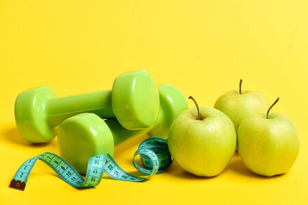 Apples in green and yellow color, green dumbbells and twisted cyan measuring tape, isolated on yellow background. Dietary and healthy lifestyle concept