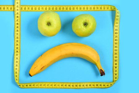 smiley pouce: Visage de fruits Moody. Smiley avec une expression triste faite de banane et de pommes isolées sur fond cyan. Concept d'émotions et de dépression Banque d'images