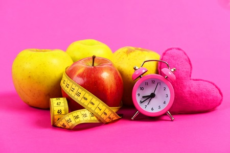 Food regime composition. Apples with yellow measuring tape in roll and pink heart with retro clock near it, isolated on bright rosy background. Concept of time for health