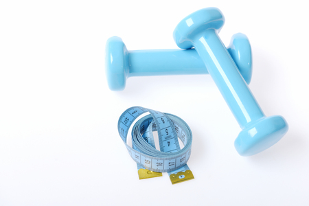 Couple of cyan blue barbells near blue tape for measuring in roll isolated on white background, top view. Concept of healthy life regime and sports