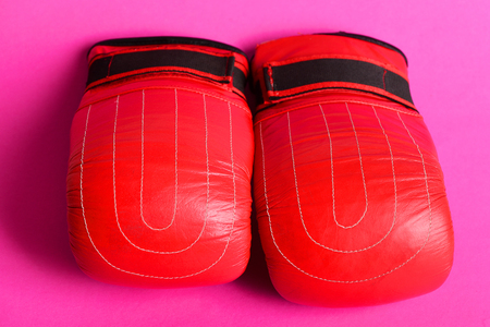 Boxing gloves in bright new red color laid and isolated on magenta pink background, close up. Fighting career start concept Stock Photo