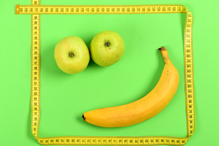 smiley pouce: Funny smiley made of food: apples for eyes and ripe banana for mouth framed with yellow measuring tape isolated on light green background. Happy face expression