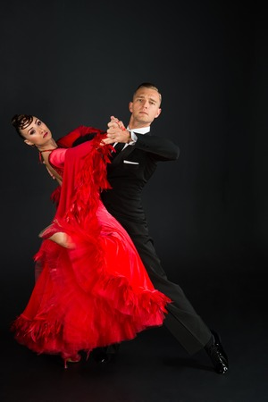 dance ballroom couple in a dance pose on black background. sensual professional dancers dancing walz, tango, slowfox and quickstep. Stock Photo