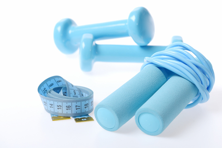 Composition of sportive lifestyle with folded cyan skipping rope, blue flexible ruler and cyan barbells on behind, isolated on white background, defocused. Fitness and shaping Stock Photo