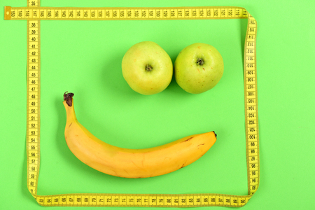smiley pouce: Face with happy expression and smile made of banana and apple fruit for mouth and eyes framed with yellow measuring tape isolated on light green background. Food art and emotions concept