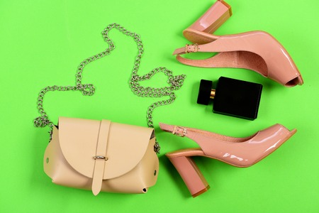Accessories for women isolated on green background, top view. Purse and shoes in light beige and pink color with black perfume. Handbag and female footwear with bottle of scent. Casual fashion concept Stock Photo