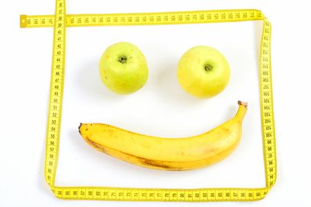 Visage avec sourire fait de fruits mûrs, encadré avec du ruban à mesurer jaune isolé sur fond blanc. Concept de régime réussi Banque d'images - 81597657