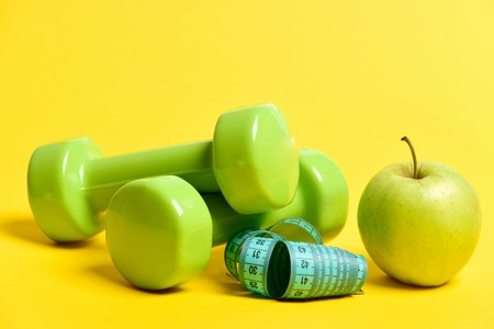 Bright sport composition. Striking green dumbbells for sports, juicy apple and cyan measuring tape isolated on yellow background. Concept of healthy regime and sports Reklamní fotografie