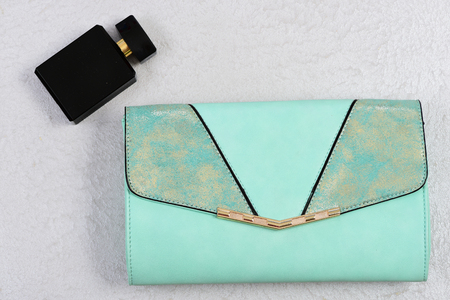 Purse in light green color and perfume. Fashionable look and design concept. Accessories in modern style on white or grey texture background. Handbag for women and bottle of scent, top view Stockfoto