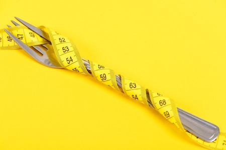 Fork made of metal tied around with yellow measuring ruler isolated on bright yellow background, copy space Stock Photo