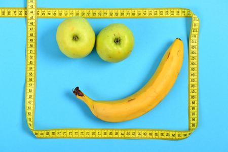 smiley pouce: Smiley fait de fruits: bouche de banane et yeux de pommes encadrées de carré de ruban à mesurer, isolé sur fond cyan. Concept de bonheur et de joie, art alimentaire