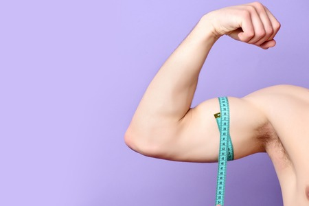 Biceps of man wrapped around by blue tape for measuring. Muscles isolated on light purple background with copy space. Diet and workout concept Stock Photo
