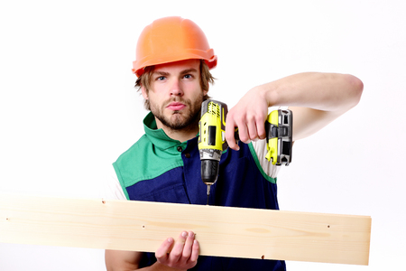 Man with concentrated face, isolated on white background. Builder in orange helmet and uniform. Work in progress and building concept. Repair worker uses yellow drill to make hole in wooden board Stock Photo
