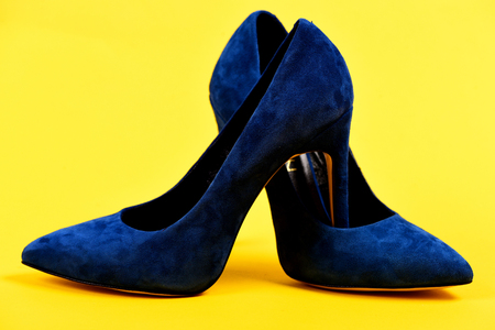 Shoes in dark blue color. Pair of formal suede female shoes, close up. Fashion, shopping and glamour concept. High heel footwear isolated on yellow background