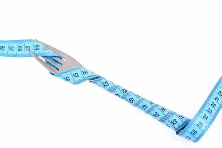 Cyan flexible ruler twisted around silver salad fork isolated on white background. Idea of pure healthy nutrition