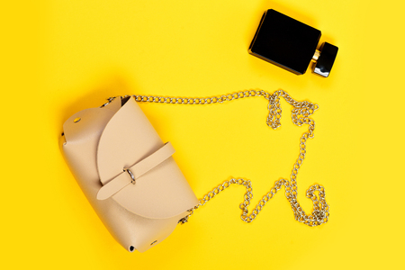Purse in light beige color and perfume. Handbag for women and black bottle of scent, top view. Accessories in modern style isolated on yellow background. Fashion and glamour concept