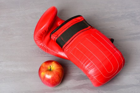 Pair of leather boxing sportswear with juicy red apple. Training and fitness concept. Sport equipment and fruit on grey texture background. Boxing gloves in red color