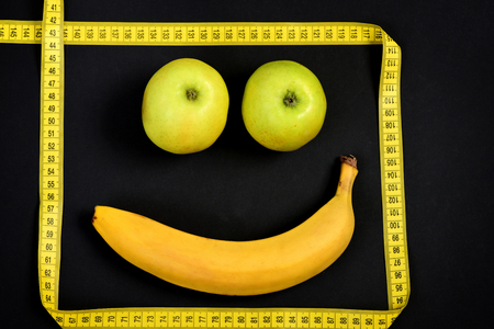 smiley pouce: Smiley with happy expression made of banana and apples framed with yellow measuring tape on black background. Concept of minimalistic art and happiness