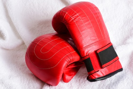 Couple of red leather mittens for boxing with black parts lying on soft white towel as background. Idea of sports equipment