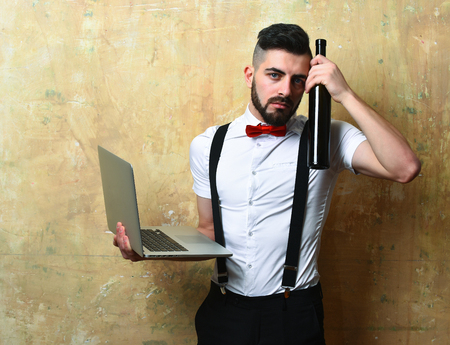 Concept of working morning after night party: man with beard and sad face expression holds laptop in one hand and bottle of wine near his had on beige background
