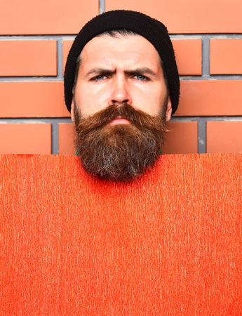 Bearded man, long beard. Brutal caucasian serious unshaven hipster in black hat with red paper sheet on brown brick wall studio background, copy space