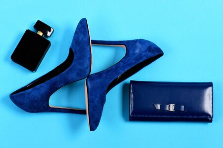 Purse and shoes in dark blue color with black perfume. Clutch and female footwear with bottle of scent. Fashion and style concept. Accessories in formal style isolated on cyan background, top view