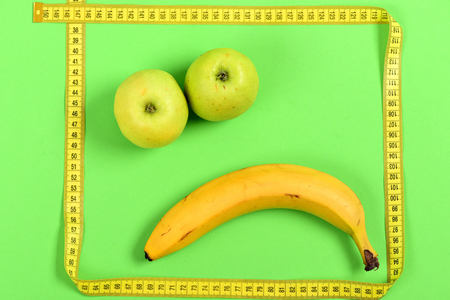 smiley pouce: Face with sad expression made of ripe fruit including apples and banana with frame of yellow flexible ruler, isolated on green background. Concept of emotions and creativity