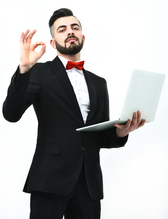 alright: Broker or businessman with beard and satisfied face expression holds high tech laptop and shows OK sign, isolated on white background. Concept of business and perfect management