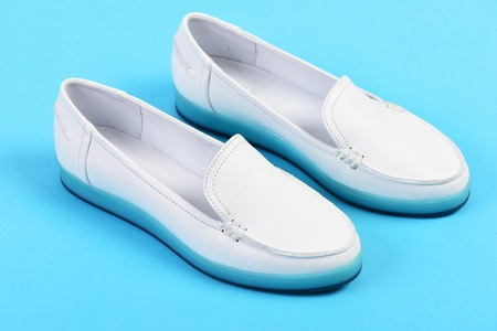 moccasin: Moccasins for women in white color. Summer fashion and casual lifestyle concept. Pair of female leather shoes isolated on cyan blue background. Low heel footwear in sports style Stock Photo
