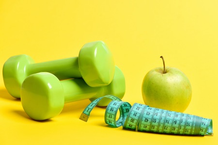 Concept of sports and health with fresh ripe apple with dumbbells and curled roll of measuring tape isolated on yellow background