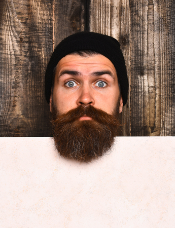 paper sheet: Bearded man, long beard. Brutal caucasian surprised unshaven hipster in black hat with white paper sheet on brown wooden vintage studio background, copy space