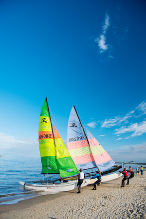 sailboard: Gdansk, Poland - September 19, 2016: windsurfer or man sportsman surfs and sails on board by wind on sea water waves surface inshore on sunny day on blue sky Editorial