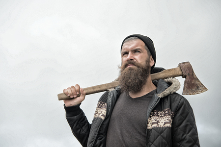 Handsome man hipster or guy with beard and moustache on serious face in hat and jacket holds rusty axe with wooden hilt outdoor on mountain top against cloudy sky on natural background, bearded man