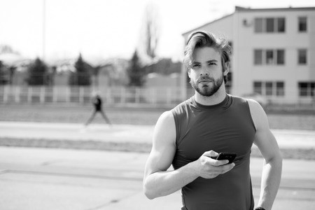 summer activity and sport. healthy lifestyle and communication, athletic bearded man or sexy handsome guy with muscular body holds mobile or cell phone training sunny outdoor, black and white