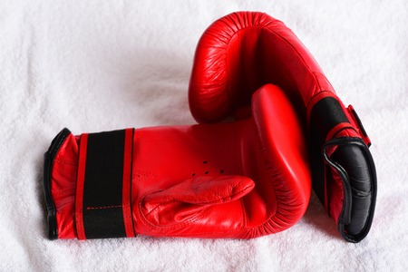 Duet of red gloves for boxing made of leather on white sweaty towel background, top view. Concept of sports and heavyweights