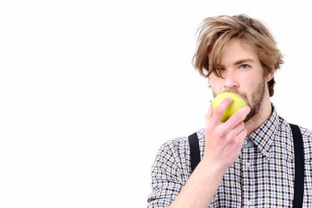 Man with beard and stylish hairdo holds and bites green apple. Macho with fresh fruit and suspenders, isolated on white background. Idea of proper nutrition. Healthy lifestyle and diet concept