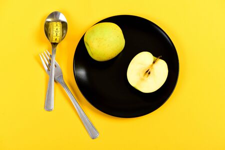 Juicy green apple lying on black ceramic plate with spoon and fork crossed nearby with rolled measuring tape, isolated on yellow background, top view