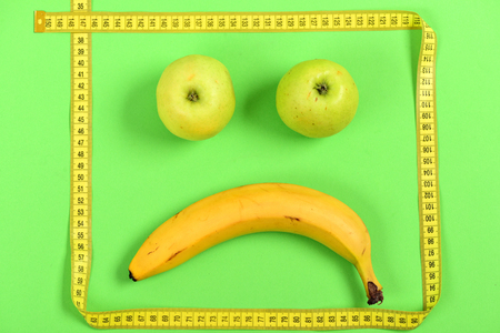 smiley: Banana and green apples with frame of yellow tape for measurement making eyes and mouth create composition of sad face, isolated on bright green background. Disappointment and emotions concept