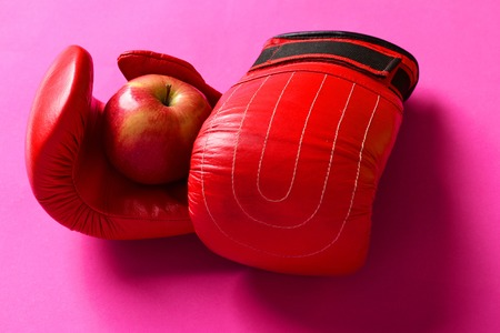Training and fitness concept. Sport equipment and fruit on magenta background. Boxing gloves in red color. Pair of leather boxing sportswear with juicy red apple Stock Photo