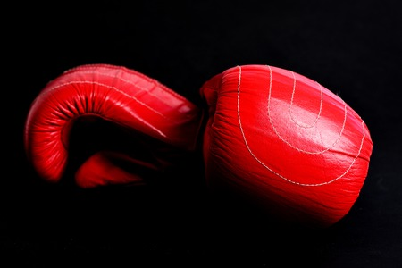 Red leather boxing gloves isolated on black background, close up. Concept of sportive lifestyle and strong fight