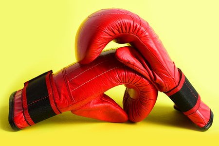 Boxing mittens made of leather in red colour with white shines isolated on yellow background. Concept of personal achivement and heavy weight sport
