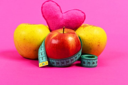 Apples and heart composition wrapped with twisted measuring tape in cyan colour isolated on bright pink background. Concept of healthy nutrition and love of food