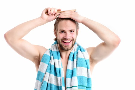 Man with naked torso, happy smiling face and beard brushes his hair. Macho with striped blue and white towel and big muscles isolated on white background. Shower time and sports concept